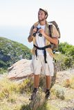Handsome hiker holding binoculars on mountain trail Stock Photography