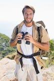 Handsome hiker holding binoculars on mountain trail Stock Photo