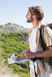 Handsome hiker holding map and compass at mountain summit Royalty Free Stock Photos