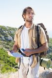 Handsome hiker holding map and compass at mountain summit Royalty Free Stock Image
