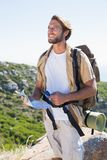 Handsome hiker holding map and compass at mountain summit Stock Images