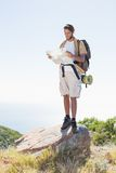 Handsome hiker holding map at mountain summit Stock Images
