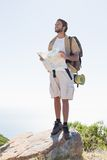 Handsome hiker holding map at mountain summit Royalty Free Stock Photography