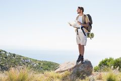 Handsome hiker holding map at mountain summit Stock Photo