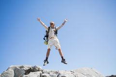 Handsome hiker jumping at the summit smiling at camera Royalty Free Stock Image