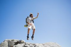 Handsome hiker jumping at the summit smiling at camera Royalty Free Stock Images