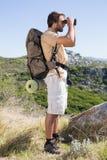 Handsome hiker looking through binoculars Stock Image