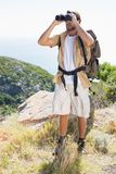 Handsome hiker looking through binoculars Royalty Free Stock Images