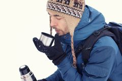 Handsome hiker man in warm clothes drinking tea in mug from thermos in winter forest. Season concept royalty free stock photo