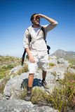 Handsome hiker standing at the summit looking around Stock Photos