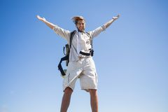 Handsome hiker standing at the summit smiling at camera Royalty Free Stock Photos