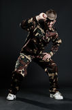 Handsome hip hop dancer in camouflage. Over dark background stock photo