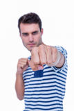 Handsome hipster attacking with his left fist Royalty Free Stock Photos
