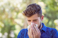 Handsome hipster blowing his nose. On a sunny day Stock Image