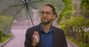 Handsome hipster businessman under the umbrella looks around carefully and smiles into camera with satisfaction in park. Handsome hipster businessman under the stock footage