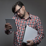 Handsome hipster busy man with many gadgets in hands. Handsome hipster busy man with many gadgets in hands on gray background royalty free stock photos