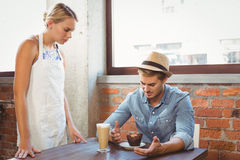 Handsome hipster complaining to blonde waitress. At coffee shop stock photo