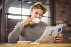 Handsome hipster drinking coffee and reading newspaper Stock Photography