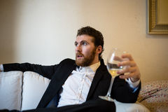 Handsome hipster elegant man holding glass of wine royalty free stock images