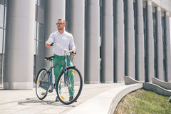 Handsome hipster enjoying city ride by bicycle. Businessman and his bicycle on city streets. The concept of the modern lifestyle of young men Stock Image