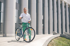 Handsome hipster enjoying city ride by bicycle. Businessman and his bicycle on city streets. The concept of the modern lifestyle of young men Stock Photography