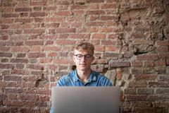 Young man successful freelancer using laptop computer for work in internet, sitting in modern co-working space. Stock Image