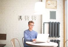 Young man writing a business plan for coffee shop on laptop computer. Handsome hipster guy keyboarding on portable net-book, sitting in cafe. Handsome male Royalty Free Stock Photos