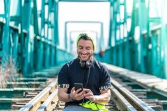 Handsome Hipster Guy Using the Cellphone and Wearing Headphones. Sitting on the Train Tracks royalty free stock photo