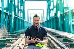 Handsome Hipster Guy Using the Cellphone and Wearing Headphones. Sitting on the Train Tracks royalty free stock image