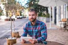 Handsome hipster guy working on digital tablet. royalty free stock images