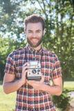 Handsome hipster holding vintage camera Royalty Free Stock Image