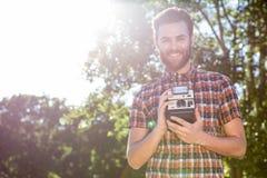 Handsome hipster holding vintage camera Royalty Free Stock Images