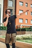 Hipster laughing while talking on the phone and pointing somewhe. Handsome hipster laughing while talking on the phone and pointing somewhere Royalty Free Stock Image