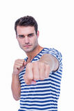 Handsome hipster looking at camera and attacking with his left fist Royalty Free Stock Photography