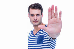 Handsome hipster looking at camera and showing stop sign with hand Royalty Free Stock Photography