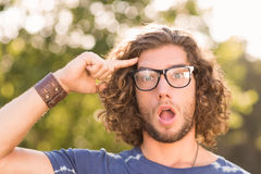 Handsome hipster looking surprised in park Stock Photo
