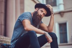 A handsome hipster male with a stylish beard with a tattoo on hi. Handsome hipster male with a stylish beard with a tattoo on his arms dressed in casual clothes royalty free stock photography