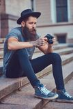 A handsome hipster male with a stylish beard and tattoo on his a. Handsome hipster male with a stylish beard and tattoo on his arms dressed in casual clothes and stock image
