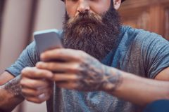 A handsome hipster male with a stylish beard and a tattoo on his. Handsome hipster male with a stylish beard and a tattoo on his arms dressed in casual clothes royalty free stock photos