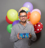 Handsome hipster man with baloons and a present in studio Stock Photography