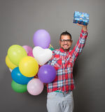 Handsome hipster man with baloons and a present in studio Royalty Free Stock Image