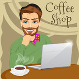 Handsome hipster man with laptop enjoying a hot coffee in coffee shop. Illustration of handsome hipster man with laptop enjoying a hot coffee in coffee shop Stock Images