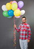 Handsome hipster man with multi-coloured baloons in studio Stock Photos