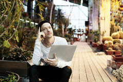 Handsome hipster man portrait working on portable laptop computer. Guy in black hat smiling in a park sunny day. Business lifestyl Royalty Free Stock Photo