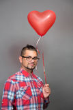 Handsome hipster man with red heart baloon in studio Royalty Free Stock Photography
