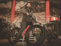 Handsome hipster man riding bike in bike  showroom. Stock Photos