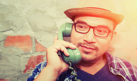 Handsome hipster man talking with retro phone on the brick backg Royalty Free Stock Photography