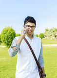 Handsome hipster modern man outdoors and talking on mobile phone. Stock Photos