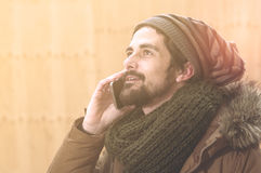 Handsome hipster modern man using smart phone warm tone filter a Stock Image