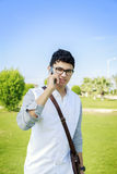Handsome hipster modern man walking outdoors and talking on mobi Royalty Free Stock Photo